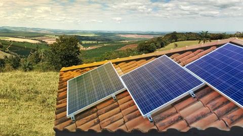 Três painéis solares num telhado