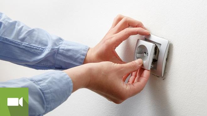 Mãos a reparar tomada solta da parede