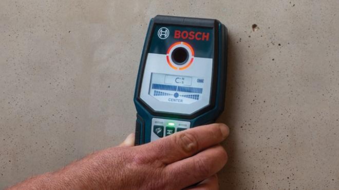 mão com detetor Bosch GMS 120 na parede
