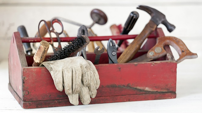 Caixa vermelha de madeira antiga com ferramentas dentro: martelo, serrote, tesoura, escova, luvas de proteção e outras