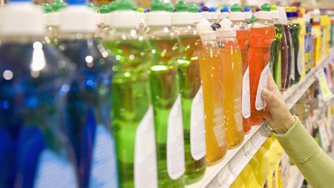 Garrafas de detergentes de diversas cores em prateleira de supermercado
