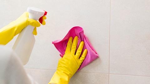 Pessoa a limpar azulejos com detergente e um pano