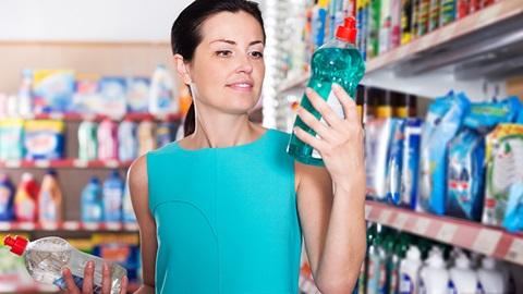 Num supermercado, no corredor dos produtos de limpeza, uma senhora segura e observa uma embalagem de detergente para lavar loiça à mão.