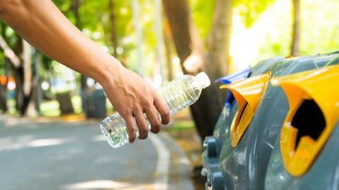 pessoa a deitar uma garrafa de plástico no ecoponto amarelo