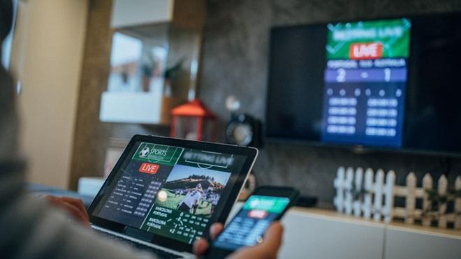 Pessoa a ver tv e a usar tablet e telemóvel
