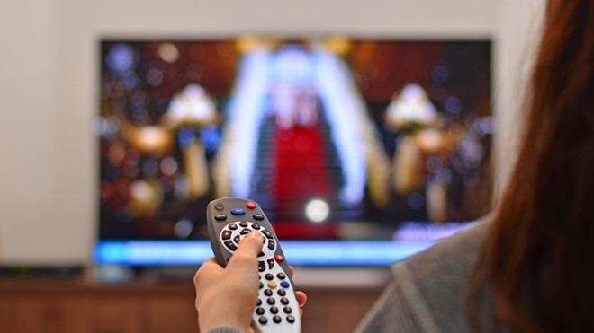 Mulher com um comando na mão em frente ao televisor
