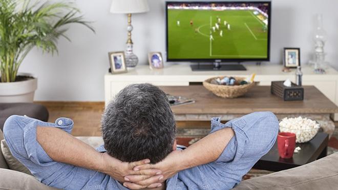 homem recostado no sofá a ver futebol na televisão