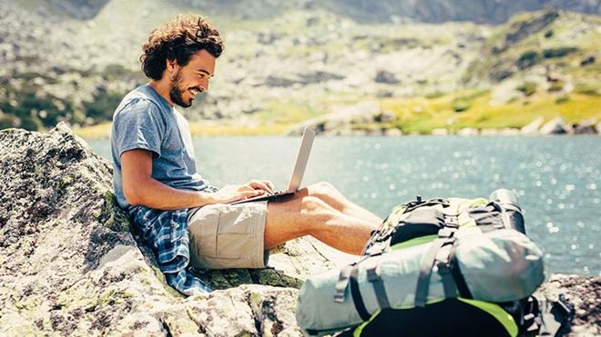 homem junto a um rio com computador a aceder à internet durante as férias