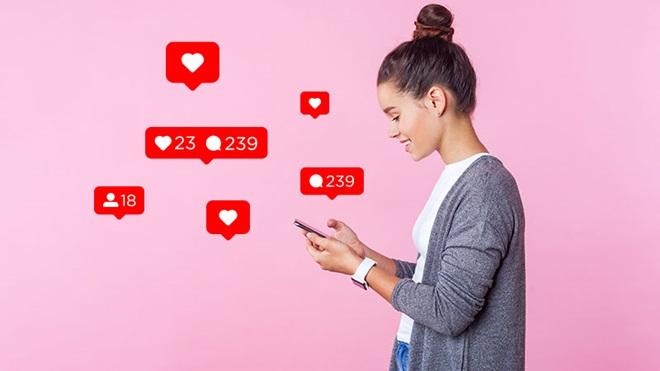 rapariga a usar telemóvel com vários ícones referentes a likes e comentários em redes sociais sobre um fundo rosa