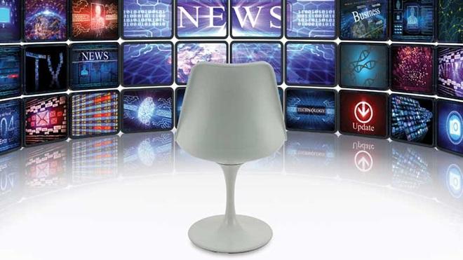 Cadeira vazia virada para muitos ecrãs de televisão
