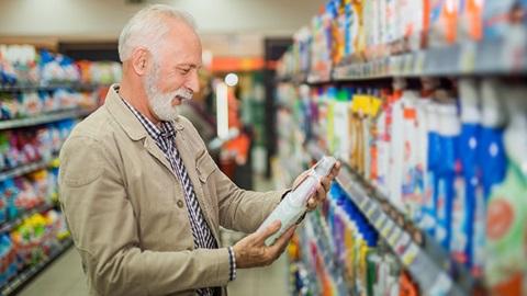 Num supermercado, no corredor dos produtos de limpeza, um senhor de idade observa a embalagem de detergente que tem nas mãos.