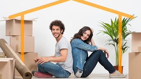 casal jovem sentado no chão da nova casa com caixotes ao lado