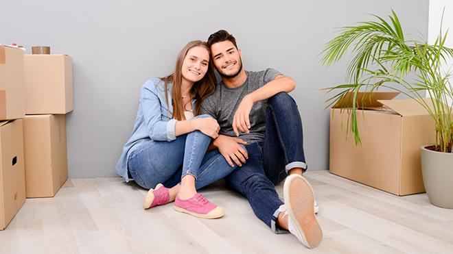 casal jovem sentado no chão de casa nova com caixotes de mudanças
