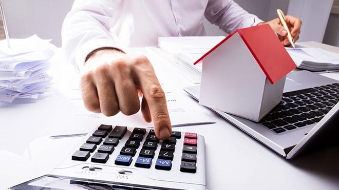 homem a utilizar calculadora para fazer contas das despesas para incluir no IRS