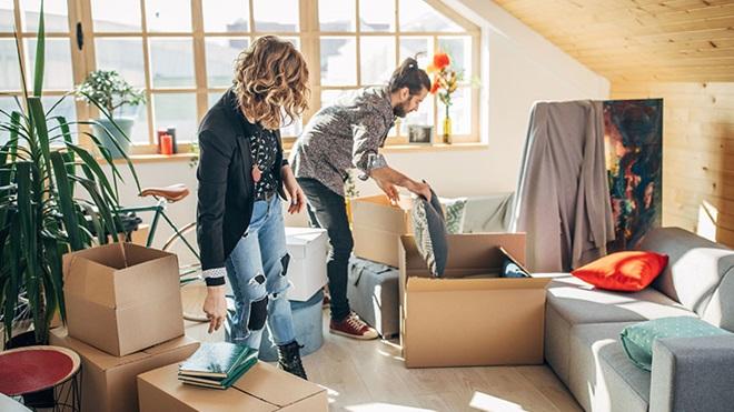 Imagem de inquilinos, um casal, a arrumar as coisas na casa arrendada em caixotes de mudanças