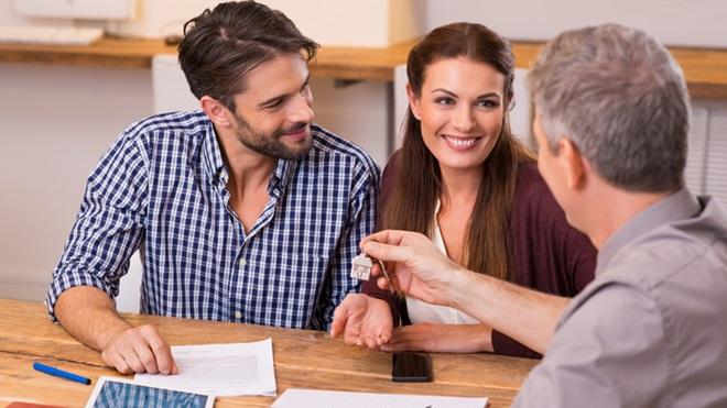 Casal assina contrato de arrendamento de casa