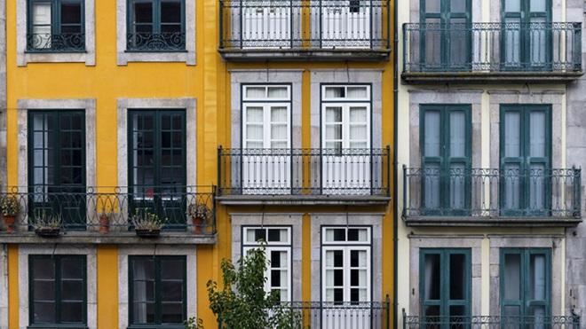 Três prédios com fachadas amarela e branca e varandas disponíveis para arrendamento