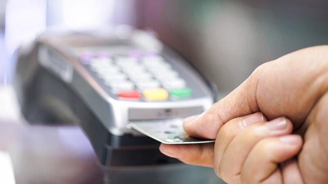 Pessoa a utilizar cartão multibanco em máquina de pagamento