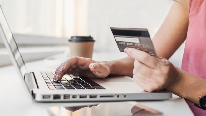 mulher no computador portátil a inserir dados do cartão de crédito