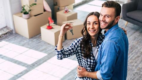Casal sorridente na casa nova e com chaves na mão