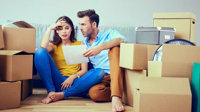 Casal rodeado por caixas de cartão e com papel na mão