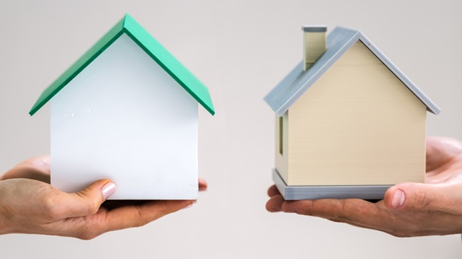 Duas mãos seguram duas casas de cartão, frente a frente