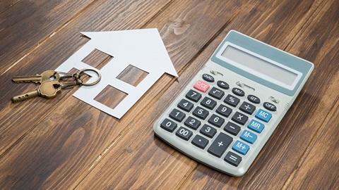 calculadora com casa e chave em cima da mesa