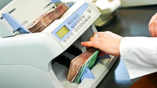 mulher a colocar notas numa máquina de contagem de notas do banco