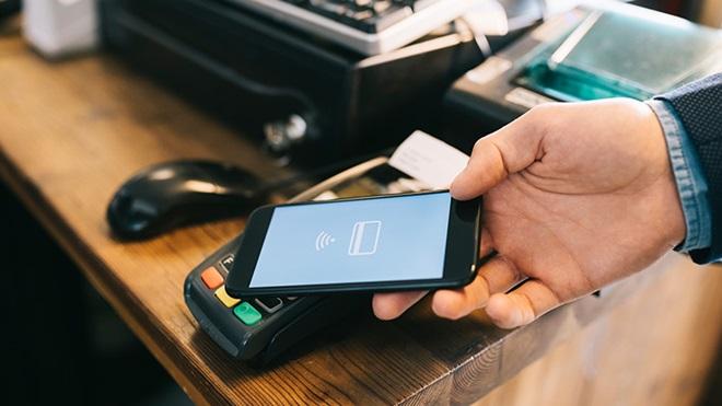 Homem a utilizar telemóvel para fazer pagamento