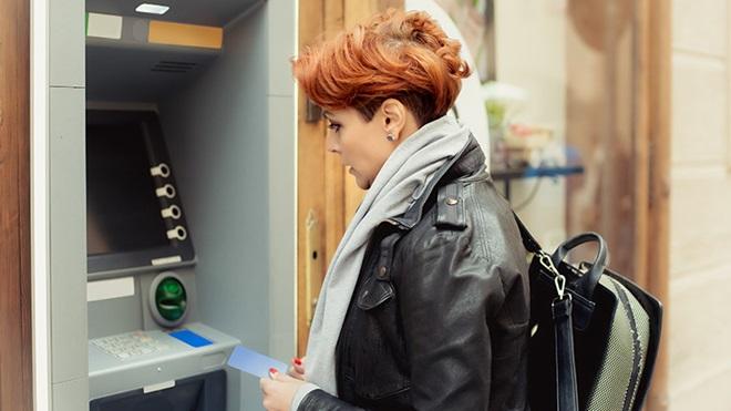 Mulher a utilizar caixa multibanco para fazer transferências interbancárias