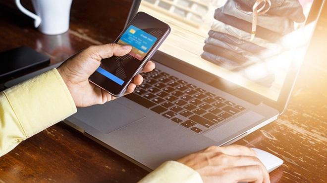 utilizador a usar smartphone e computador portátil para compras online
