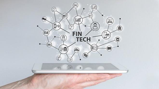 mão segura tablet com icones alusivos a empresas fintech