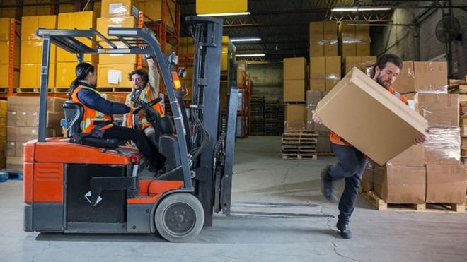 máquina empilhadora com trabalhadores a conversar num armazém