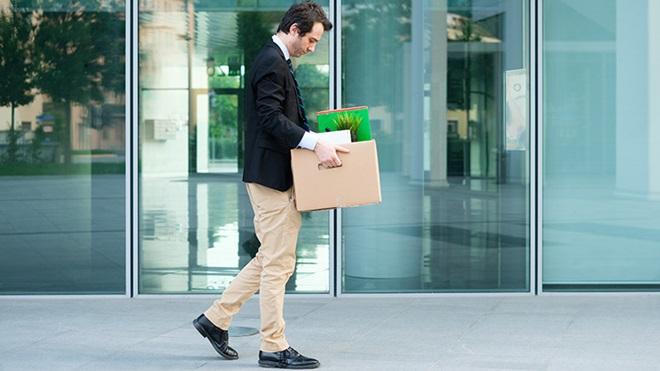 homem despedido a andar na rua com caixote contendo objetos do trabalho