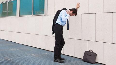 homem despedido do emprego desolado encostado a uma parede