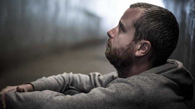 homem de perfil sentado no chão a olhar para cima com ar triste e preocupado