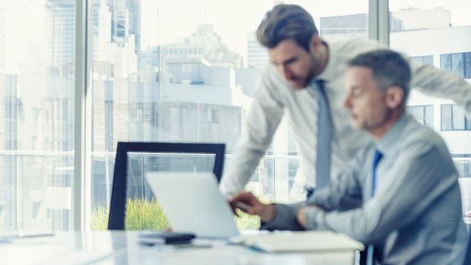 dois homens juntos no escritório a olhar e a apontar para o ecrã de um computador