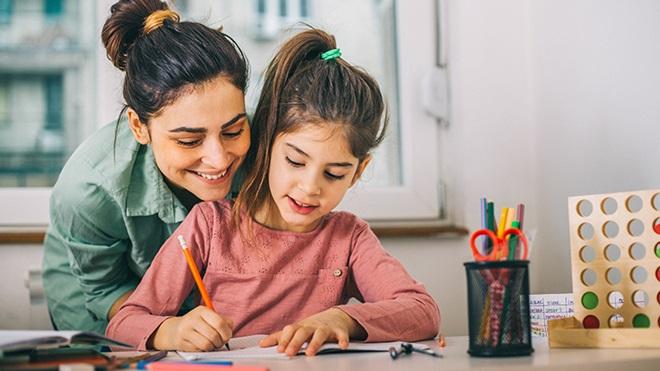 mãe a ajudar filha a fazer os trabalhos