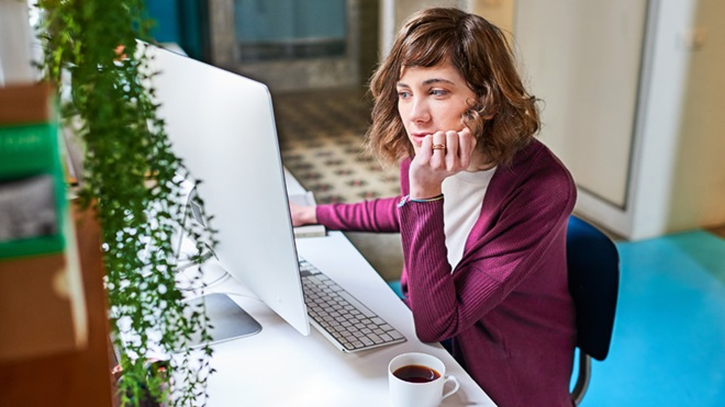 mulher sentada à secretária a tratar do subsídio de desemprego no computador