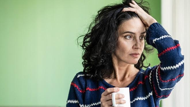 Mulher desempregada com uma caneca na mão e um ar preocupado
