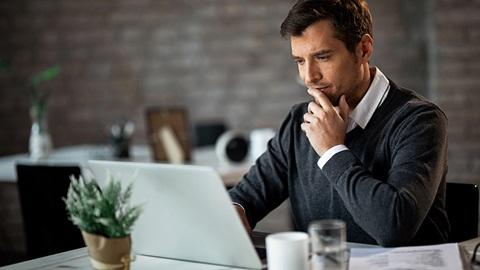 homem sentado numa mesa ao computador