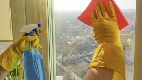 empregada doméstica com luvas amarelas limpa vidro