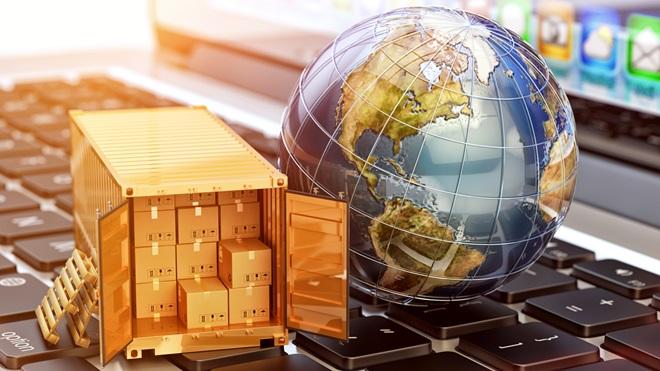 um globo terrestre e um pequeno camião de entrega de encomendas em cima de um teclado de computador