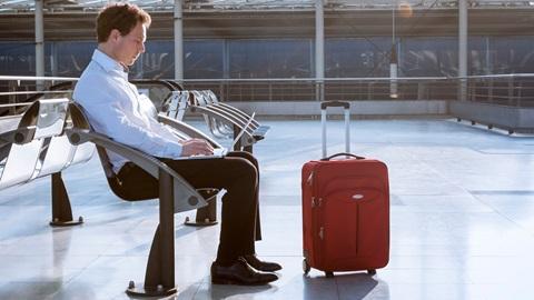 homem sentado na sala de espera do aeroporto a trabalhar num computador portátil