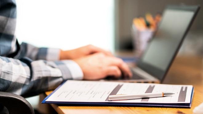 mãos ao computador numa secretária a preencher documentos