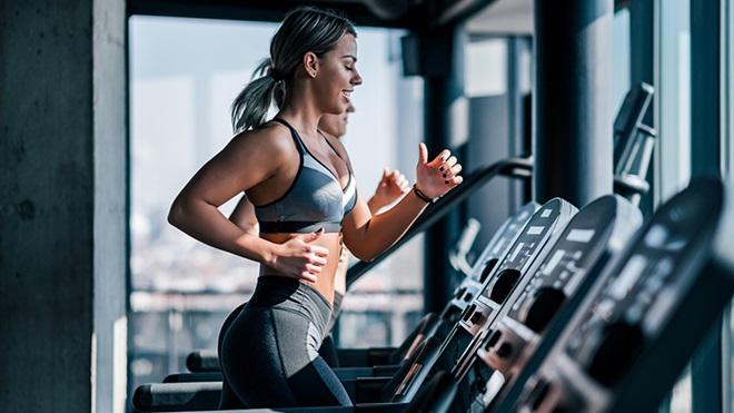 Mulher a correr numa passadeira num ginásio