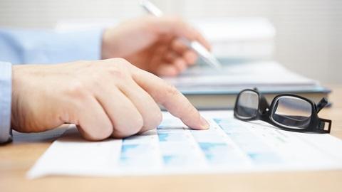 mãos de um homem a segurar uma caneta e a assinalar informação num papel