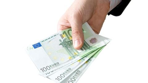 Mão de homem segura várias notas de 100 euros