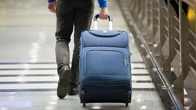 homem transporta mala com rodas no aeroporto