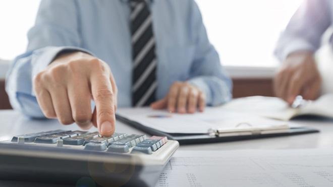 homem em escritório a fazer cálculos de IRS
